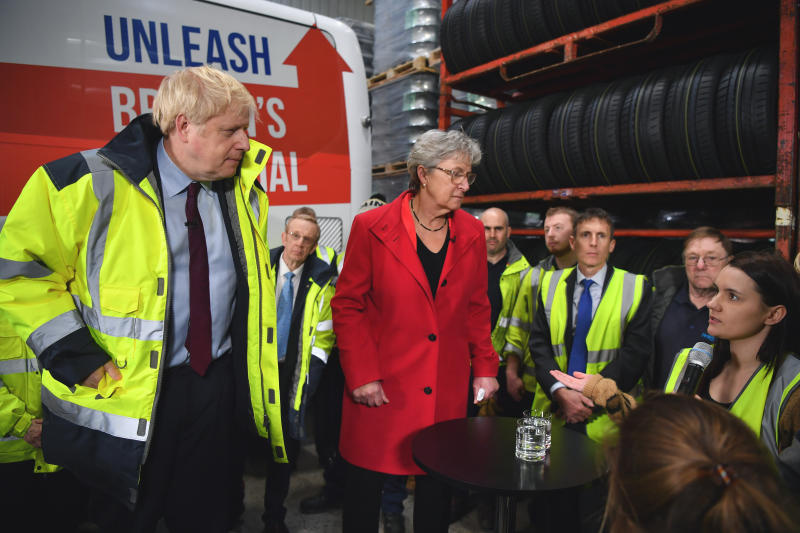 A member of staff Page Hood, right, asks Britain's Prime Minister Boris Johnson, left, a question regarding fake news websites during a question and answer session, part of a General Election campaign visit to Ferguson's Transport in Washington, England, Monday, Dec. 9, 2019. Britain goes to the polls on Dec. 12. (Ben Stansall/Pool Photo via AP)