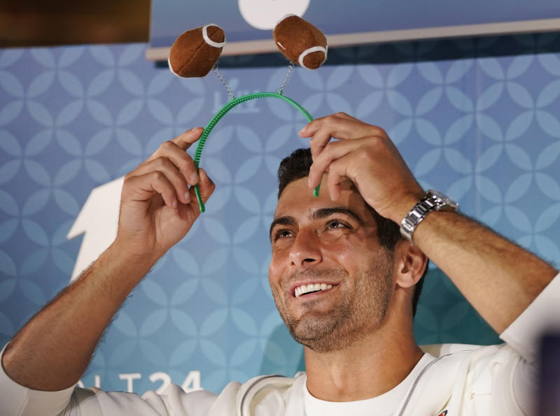 San Francisco 49ers' Jimmy Garoppolo puts a football hairband during Opening Night for the NFL Super Bowl 54 football game Monday, Jan. 27, 2020, at Marlins Park in Miami. (AP Photo/David J. Phillip)