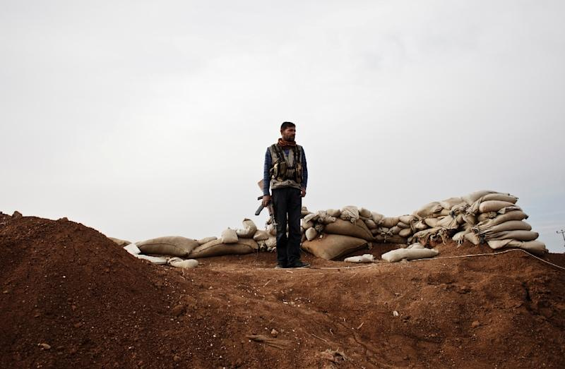 A member of the Kurdish Committees for the Protection of the Kurdish People stands in the Syrian Kurdish town of Ras al-Ain, next to the Turkish border (AFP Photo/Achilleas Zavallis)