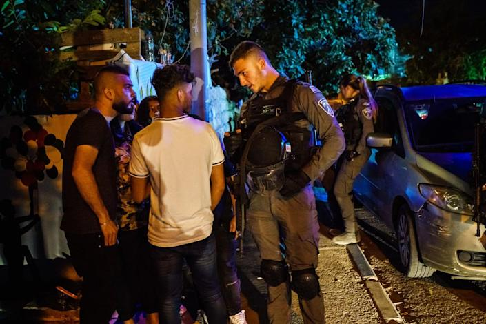 An Israeli security officer questions young residents on the streets of the Sheikh Jarrah neighborhood in East Jerusalem