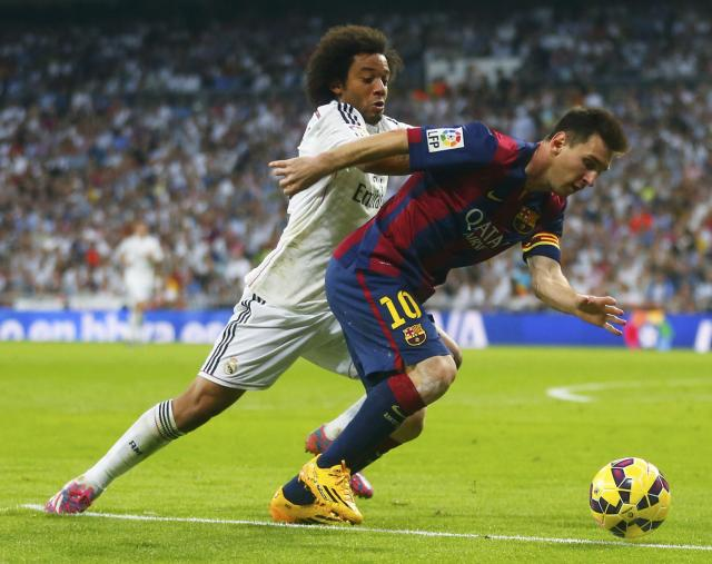 "Barcelona's Lionel Messi (R) is challenged by Real Madrid's Marcelo during their Spanish first division ""Clasico"" soccer match at the Santiago Bernabeu stadium in Madrid October 25, 2014. REUTERS/Juan Medina (SPAIN - Tags: SOCCER SPORT)"