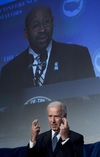 Vice President Joe Biden crosses his fingers as U.S. Conference of Mayors President, Philadelphia Mayor Michael Nutter projected on a monitor, makes his remarks at the U.S. Conference of Mayors 81st winter meeting in Washington, Thursday, Jan. 17, 2013. (AP Photo/Manuel Balce Ceneta)