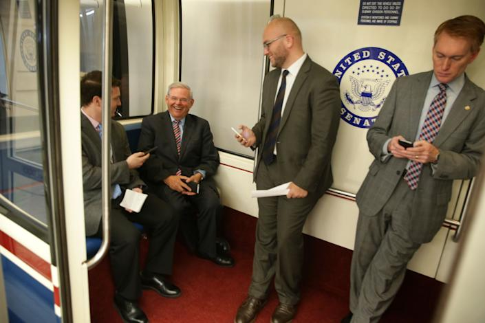 Sen. Robert Menendez (D-N.J.), second from left, smiles as he rides a Senate subway with a member of the press, left, after a vote April 23, 2015, to confirm Loretta Lynch as the next U.S. attorney general.