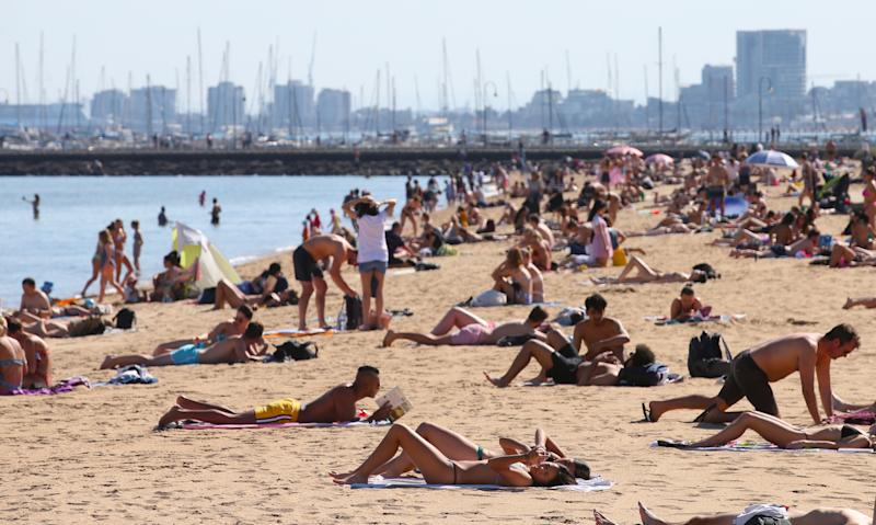 People laying in the sun on St Kilda Beach in Melbourne as 50 degree days predicted for Australia.