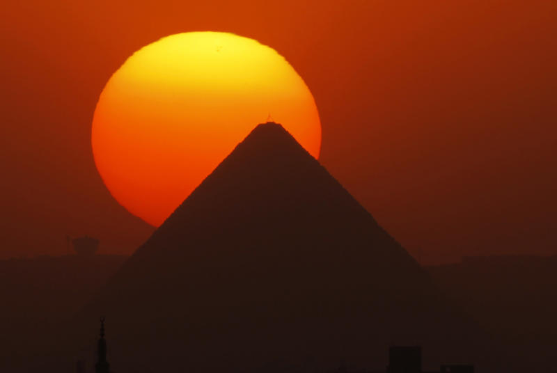 The sun sets behind the Great Pyramid in Giza, Egypt, Friday, April 26, 2013. Elsewhere, dozens of mostly masked protesters are hurling stones and firebombs in clashes with riot police at Egypt's presidential palace in a Cairo suburb. Protests have become a weekly routine in Egypt, as the country has plunged in turmoil during most of the past two years since 2011 uprising which ousted longtime president Hosni Mubarak out of power. (AP Photo/Amr Nabil)