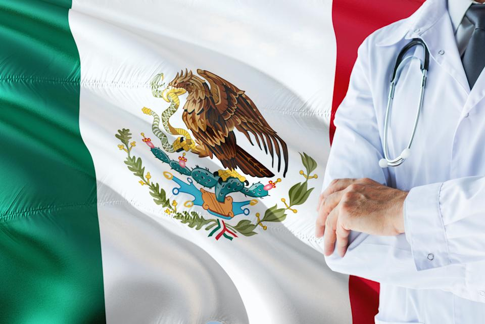 Mexican Doctor standing with stethoscope on Mexico flag background. National healthcare system concept, medical theme.