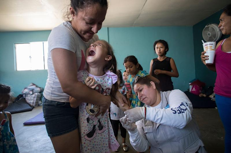 MEXICALI, Mexico – Marisela Lopez, 28, holds her 6-year-old daughter, Maritza Salazar Lopez, as Andrea Delgado with the Baja California state health ministry draws blood from her finger on June 24, 2019. Delgado was testing for malaria at the migrant shelter Casa de Ayuda Alfa y Omega.