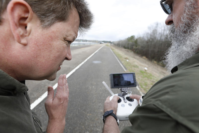 John Weaver, an engineer who works with the Oktibbeha County, left, and Tim Gordy, the air coordinator with the Mississippi Emergency Management Agency, review drone footage of the bottom of the Oktibbeha County Lake dam near Starkville, Miss., Wednesday, Jan. 15, 2020. The rain-swollen lake is keeping heavy pressure on a dam that is in danger of failing, state and local officials said Wednesday. A breach would affect an estimated 130 properties and nine highways. (AP Photo/Rogelio V. Solis)