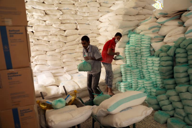 FILE PHOTO: Workers prepare foodstuff for beneficiaries at a food distribution center supported by the World Food Program in Sanaa