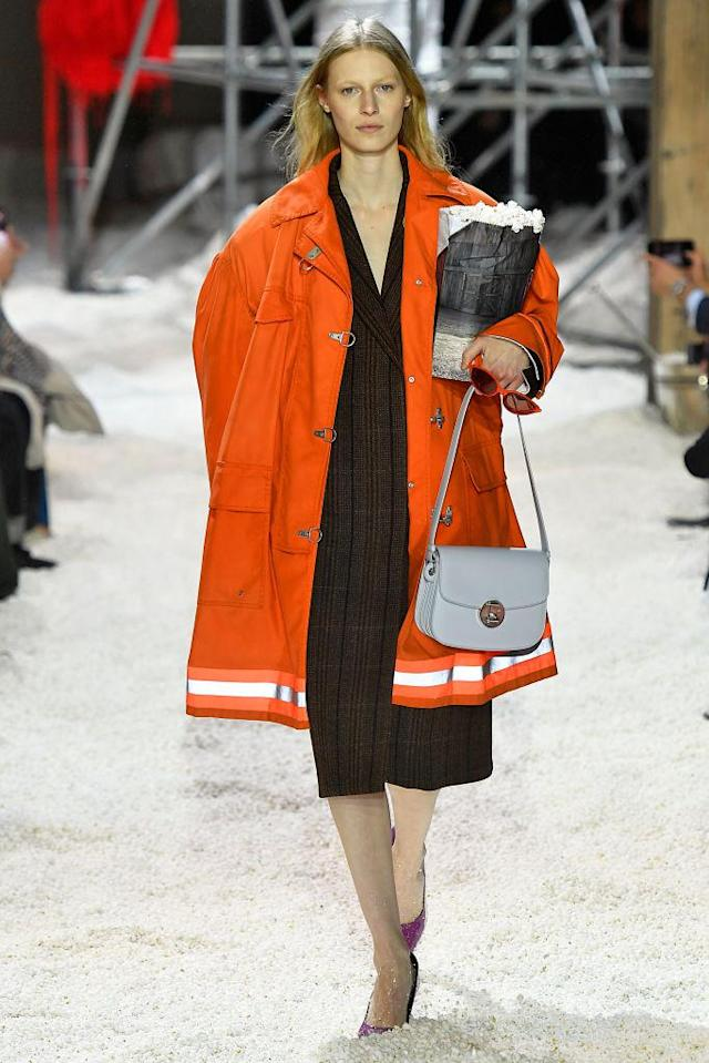 <p>A model wears an oversize orange safety coat while clutching a bag of popcorn at the Calvin Klein fall 2018 show. (Photo: Getty Images) </p>