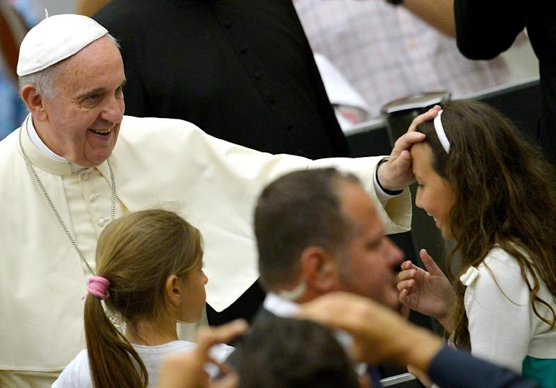 Pope Francis blesses a girl as he arrives for his weekly audience in the Paul VI hall on August 6, 2014 in the Vatican