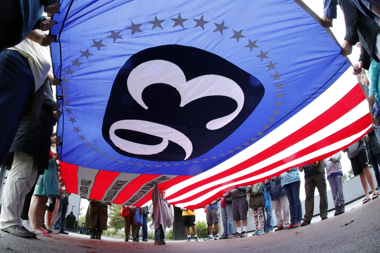 <p>Visitors to the Flight 93 National Memorial in Shanksville, Pa., hold a giant Flight 93 flag during a moment of remembrance Monday, Sept. 10, 2018, as the nation marks the 17th anniversary of the Sept. 11, 2001, attacks. (AP Photo/Gene J. Puskar) </p>