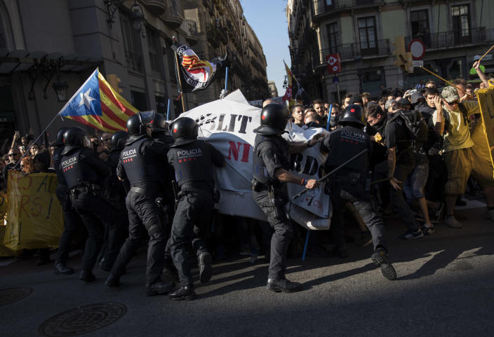 Catalan police officers try to stop pro independence demonstrators, on their way to meet demonstrations by member and supporters of the National Police and Guardia Civil in Barcelona on Saturday, Sept. 29, 2018. (AP Photo/Emilio Morenatti)