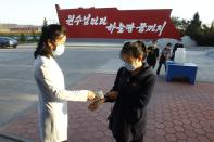 Hygienic and anti-epidemic officials disinfect and check the temperature of people outside the entrance to Songdowon General Foodstuff Factory in the city of Wonsan, Kangwon Province, North Korea DPRK, on Wednesday, Oct., 28, 2020. (AP Photo/Jon Chol Jin)