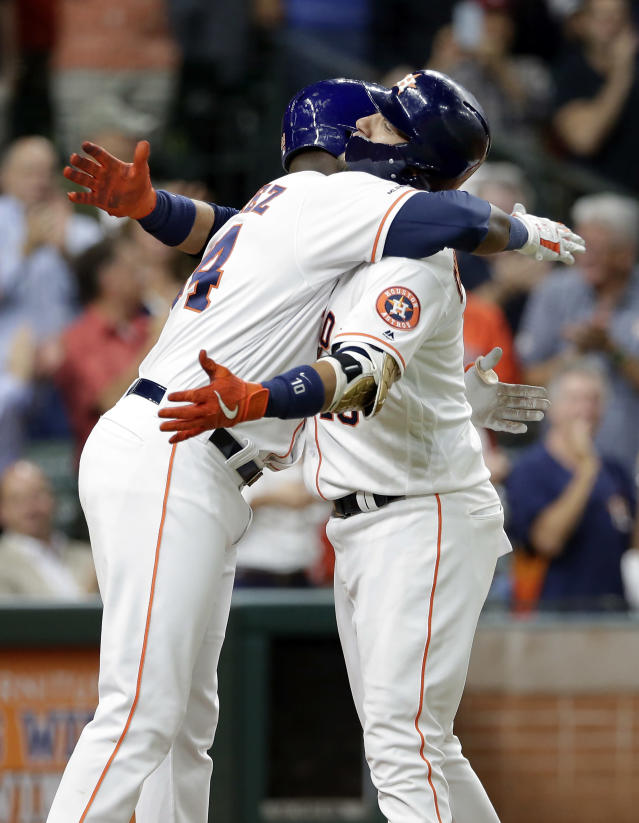 Houston Astros' Yordan Alvarez, left, and Yuli Gurriel, right, hug at home plate after they both scored on Gurriel's two-run home run during the fifth inning of a baseball game against the Texas Rangers Wednesday, Sept. 18, 2019, in Houston. (AP Photo/Michael Wyke)