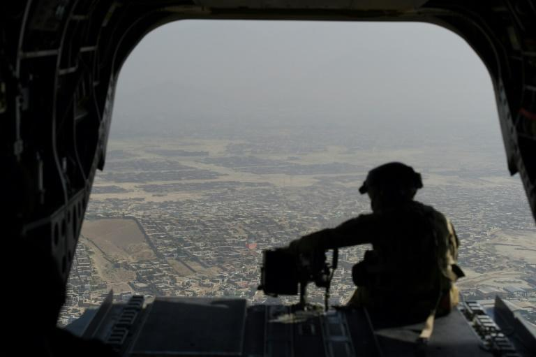 A US soldier sits on the ramp of a Chinook helicopter while flying over Kabul. Washington has announced plans to hasten the withdrawal of US forces