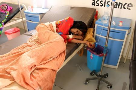 A cholrea patient lies on a bed as she receives medical care at a health center in the village of Islim, in the northwestern province of Hajjah
