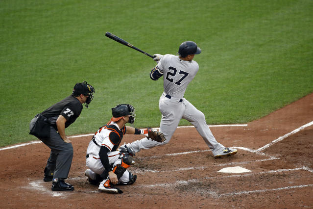New York Yankees' Giancarlo Stanton follows through on an RBI single in front of umpire Jim Reynolds and Baltimore Orioles catcher Caleb Joseph during the third inning of a baseball game Wednesday, July 11, 2018, in Baltimore. (AP Photo/Patrick Semansky)