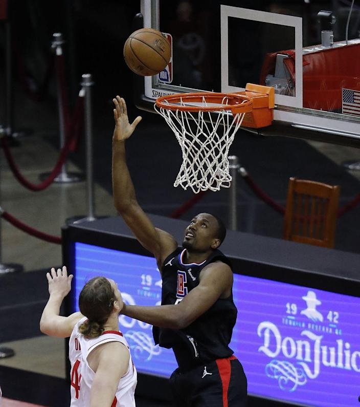 The Clippers' Serge Ibaka shoots a layup over the Rockets' Kelly Olynyk on May 14, 2021.