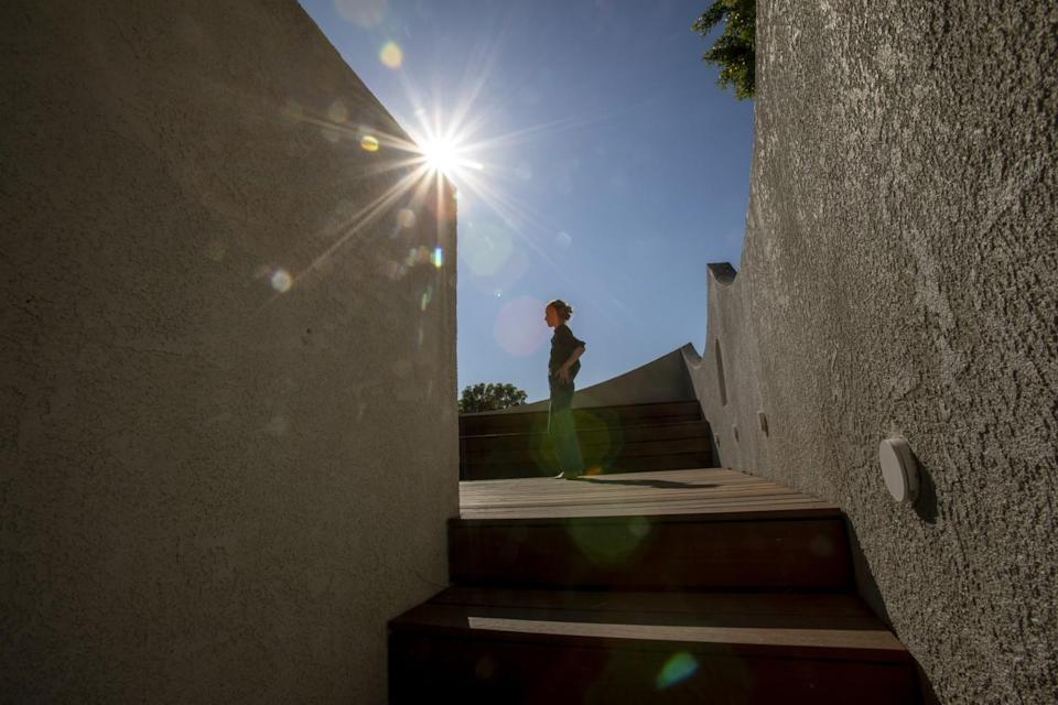 A woman stands at the top of a stairway, silhouetted against the sun