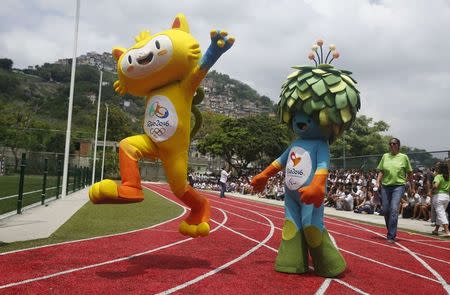 The unnamed mascots of the Rio 2016 Olympic (L) and Paralympic Games are pictured with the Morro dos Prazeres slum in the background during its presentation in Rio de Janeiro, November 24, 2014. REUTERS/Pilar Olivares
