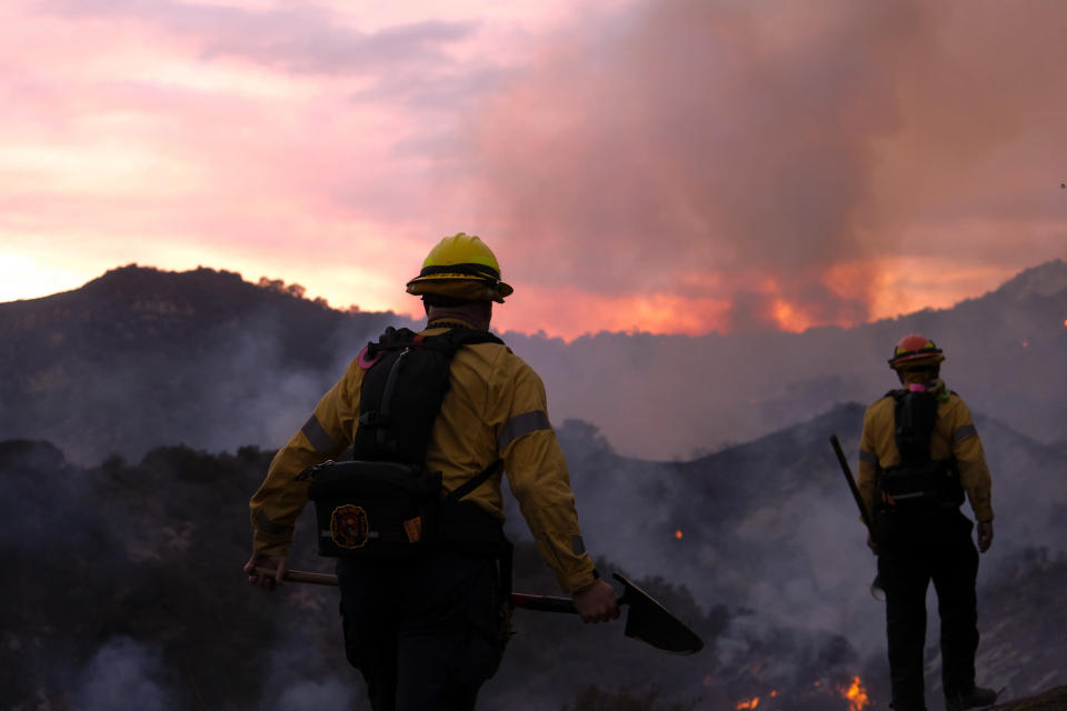 Firefighters keep watch as smoke rises from a brush fire scorching at least 100 acres in the Pacific Palisades area of Los Angeles, Saturday, May 15, 2021. (AP Photo/Ringo H.W. Chiu)