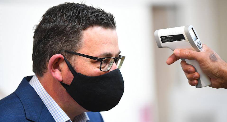 Daniel Andrews getting his temperature checked while wearing a mask.