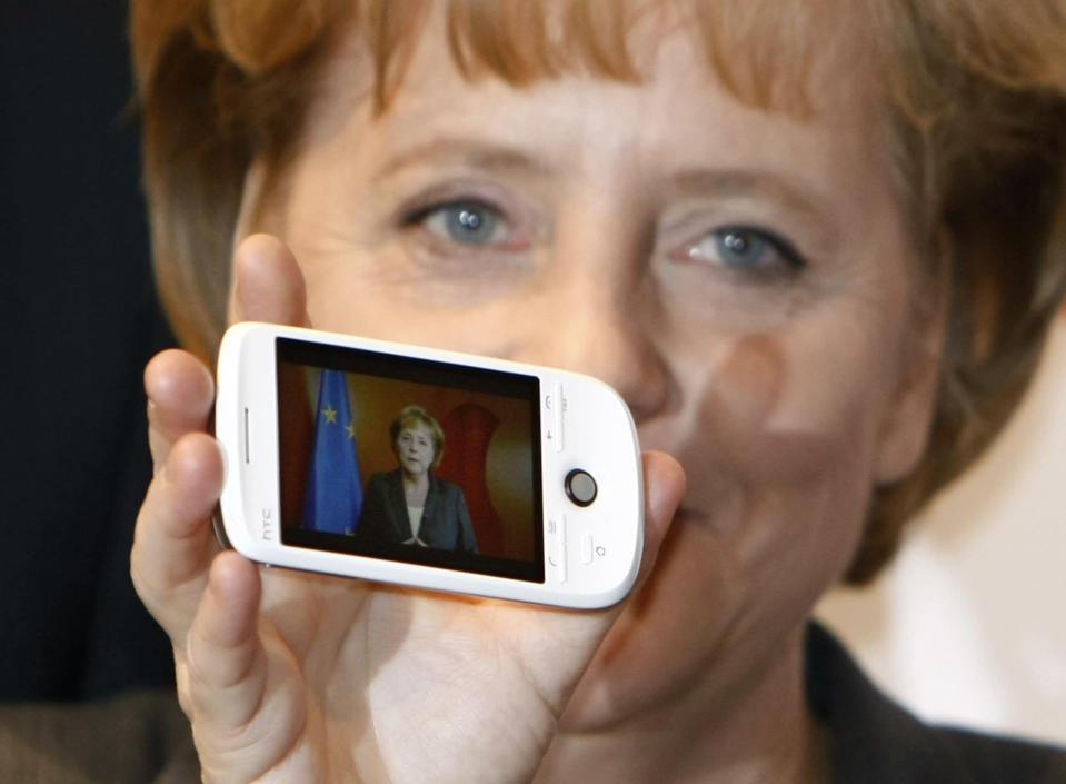 FILE - In this Tuesday, March 3, 2009 file photo German Chancellor Angela Merkel holds a cell phone with a photo of her on the screen during her opening walk at the CeBIT in Hanover, northern Germany. Cybersecurity researchers in Europe say they've discovered a flaw in an encryption algorithm used by cellphones that may have allowed attackers to eavesdrop on some data traffic for more than two decades. In a paper published Wednesday, researchers from Germany, France and Norway said the flaw affects the GPRS mobile data standard. (AP Photo/Joerg Sarbach, file)