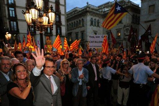 <p>Catalonia's regional president Artur Mas (second left) and his wife Elena Rakosnic (left) wave to a crowd of supporters holding Catalan independence flags in Plaza Sant Jaume square in Barcelona on September 20. Spain's government announced Friday it will reform how the debt-struck regions are financed, a day after flatly rejecting Catalonia's bid for fiscal independence.</p>