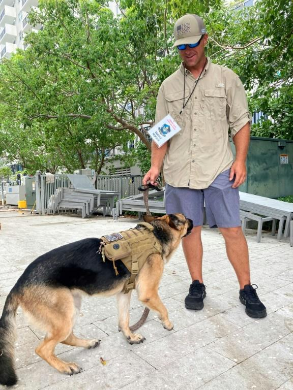 United Cajun Navy volunteer Patrick Williamson plays with his therapy dog Gracie in Surfside, Florida on June 28, 2021