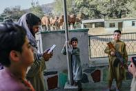 A group of Taliban gunmen offered their rifles to boys as young as eight, who took snaps with their mobile phones (AFP/BULENT KILIC)