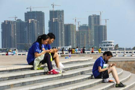 People sit on steps against a backdrop of residential buildings under construction, in Haikou