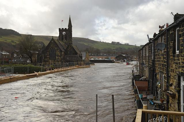 Newly constructed flood defences are seen here (left) beside the River Calder in Mytholmroyd, but proved insufficient to prevent the river bursting its banks and flooding the village. (Oli Scarff/AFP via Getty Images)