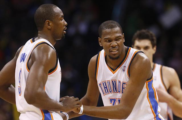 Oklahoma City Thunder forward Kevin Durant (35) grimaces as he is helped up by teammate Serge Ibaka, left, following a fall in the third quarter of an NBA basketball game against the Philadelphia 76ers in Oklahoma City, Tuesday, March 4, 2014. Oklahoma City won 125-92. (AP Photo/Sue Ogrocki)
