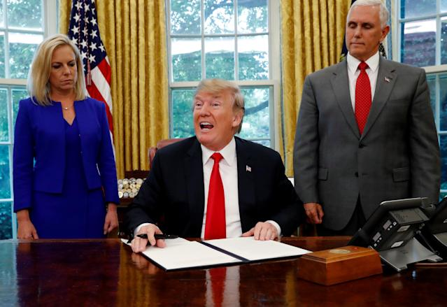 President Trump after signing an executive order on immigration policy, with DHS Secretary Kirstjen Nielsen and Vice President Mike Pence at his side, June 20, 2018. (Photo: Leah Milllis/Reuters)