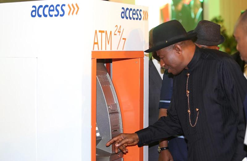 Nigerian President Goodluck Jonathan tries to make cash withdrawal with his electronic identity card during the launching of the cards in Abuja on August 28, 2014 (AFP Photo/Philip Ojisua)
