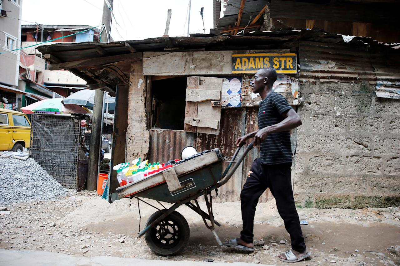 A man pushes a wheelbarrow through a street at Okepopo district in Nigeria's commercial capital Lagos April 26, 2017. REUTERS/Akintunde Akinleye