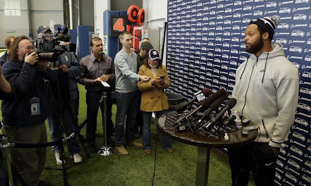 Seattle Seahawks defensive end Michael Bennett, right, talks to reporters, Monday, March 10, 2014, at the team's headquarters in Renton, Wash. The Seahawks announced Monday that Bennett, who was one of the top NFL football free agents this year, had signed a multi-year deal with the Super Bowl champion Seahawks. (AP Photo/Ted S. Warren)