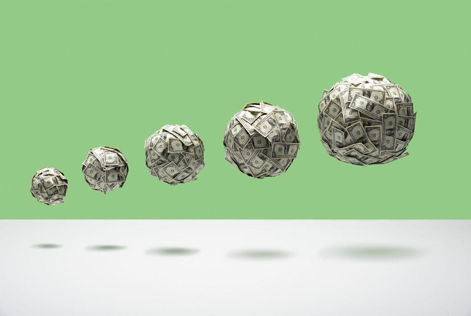 An image of growing balls of money floating in mid air.
