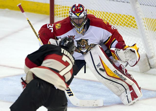 Ottawa Senators center Kyle Turris (7) shoots the puck at Florida Panthers goalie Scott Clemmensen during second-period NHL hockey game action on Thursday, Dec. 19, 2013, in Ottawa, Ontario. (AP Photo/The Canadian Press, Adrian Wyld)