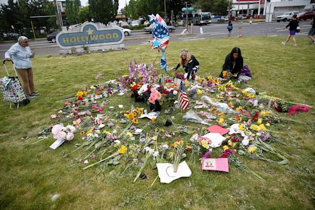 <p>Portland residents Sedona Soulfire, 41, center, and Kat Ablola, 38, right, arrange flowers at a makeshift memorial for two men who were killed on a commuter train while trying to stop another man from harassing two young women who appeared to be Muslim, at the Hollywood Transit Station in Portland, Ore., May 29, 2017. (Terray Sylvester/Reuters) </p>