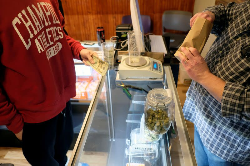 FILE PHOTO: An employee measures from a jar of marijuana on sale at the Greenstone Provisions in Ann Arbor