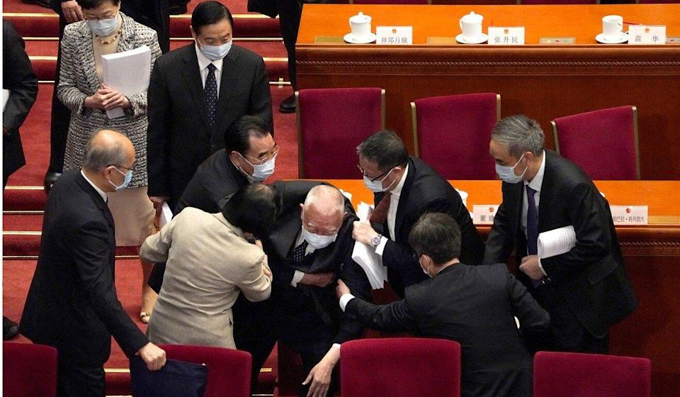 Former Hong Kong chief executive Tung Chee-hwa is aided by colleagues after falling at the opening session of China's National People's Congress in March. Photo: AP