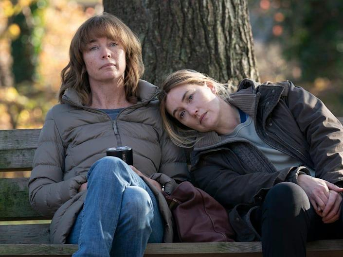 """Two women sitting on a park bench in an episode of """"Mare of Easttown."""""""