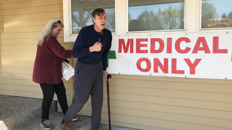 In this April 26, 2019, photo, medical marijuana cardholder Scott Donnelly, assisted by his wife and licensed caregiver, Vicki Poppen, leaves Western Oregon Dispensary in Sherwood, Ore., after buying medical marijuana to treat muscle spasms caused by his multiple sclerosis. Donnelly visits the medical-only dispensary once a week and relies on it for the cannabis that eases his tremors long enough that he can fall asleep. The dispensary is one of two medical-only shops left in Oregon. (AP Photo/Gillian Flaccus)