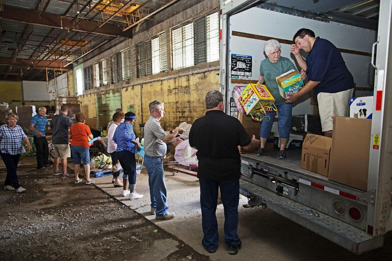 Westwego Senior Center co-ordinator, Brant Fonseca, right, leads a team of volunteers who are unloading a truck full of donated goods to be distributed to flood victims through the Healing Place Church in Denham Springs, La., Wednesday, Aug. 24, 2016. Volunteers have served thousands of free meals and passed out carloads of clothes, food, cleaning supplies and other essentials. (AP Photo/Max Becherer)