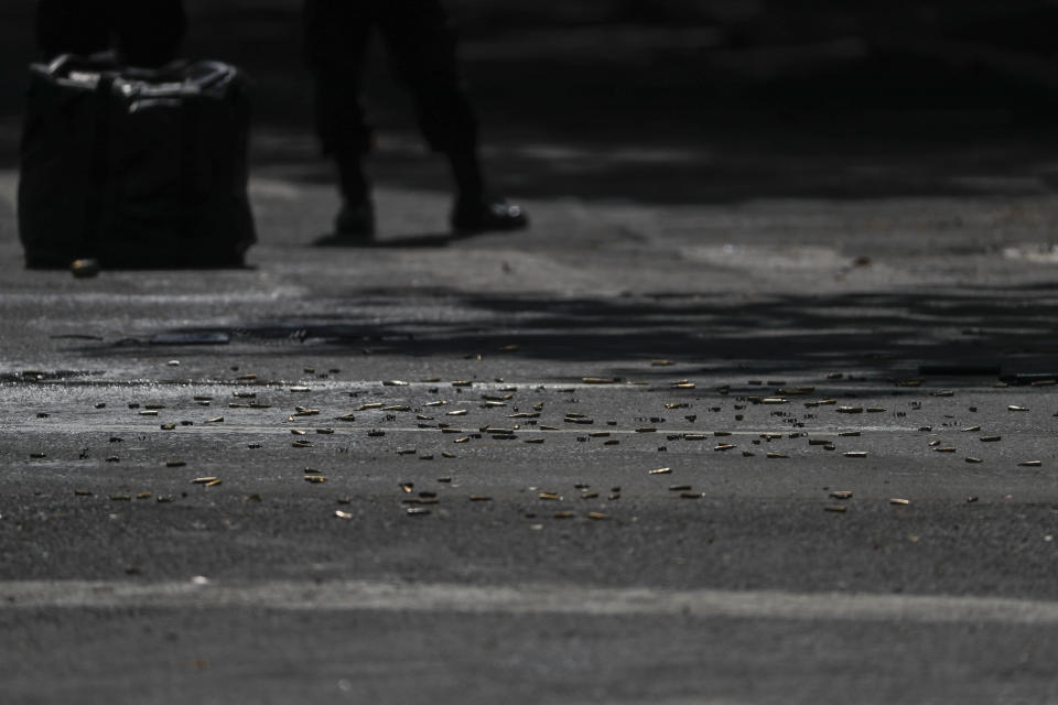 Cartridges carpet the pavement at the scene where the Mexican capital's police chief was attacked by gunmen in Mexico City, Friday, June 26, 2020. Heavily armed gunmen attacked and wounded Omar García Harfuch in an operation that left several dead. (AP Photo/Rebecca Blackwell)
