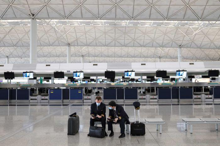 Two pilots in face masks sit in an empty terminal