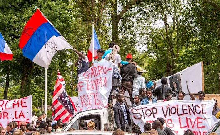 """People hold upside down US and Russian flags during a demonstration, entitled """"March for dignity"""", of migrants and activists in Calais, northern France, on World Refugee Day on June 20, 2015 (AFP Photo/Philippe Huguen)"""