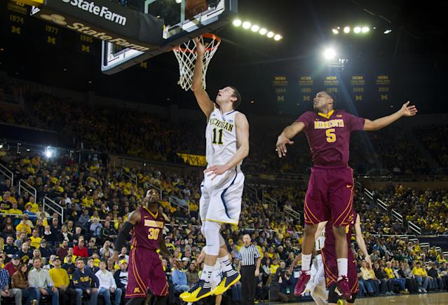 Michigan guard Nik Stauskas (11) makes a layup while defended by Minnesota guard Daquein McNeil (5) during the first half of an NCAA college basketball game in Ann Arbor, Mich., Saturday, March 1, 2014. (AP Photo/Tony Ding)